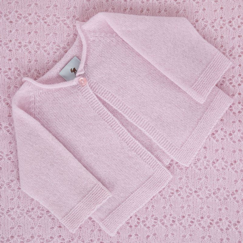 Pink cashmere baby cardigan on shawl