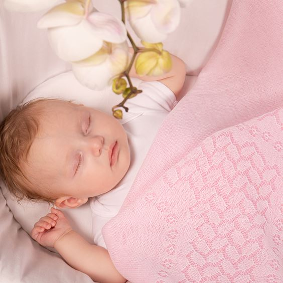 baby in crib with pink blanket