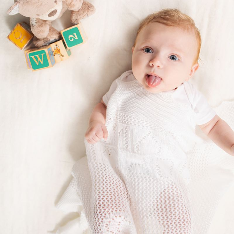 baby wrapped in white teddy alphabet shawl